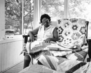 Black and White Photo of Rosie Lee Wilkins with her quilts.